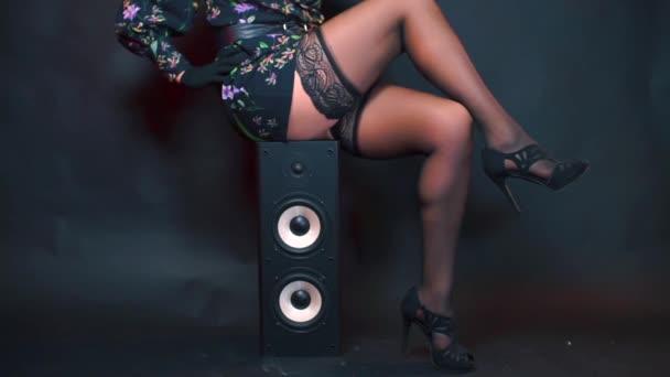 Žena v punčochách sedí na reproduktoru na perverzní párty.