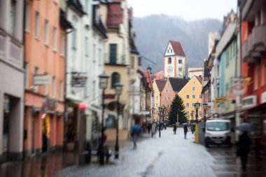 Beautiful vibrant multicolored downtown picture of street in Fussen, Bayern, Bavaria, Germany, with tourists and people walking near shop-windows and restaurants, houses in bavarian style