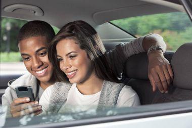Teenagers using mobile phone in car