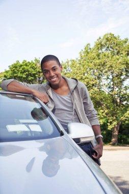 Teenage boy standing near car