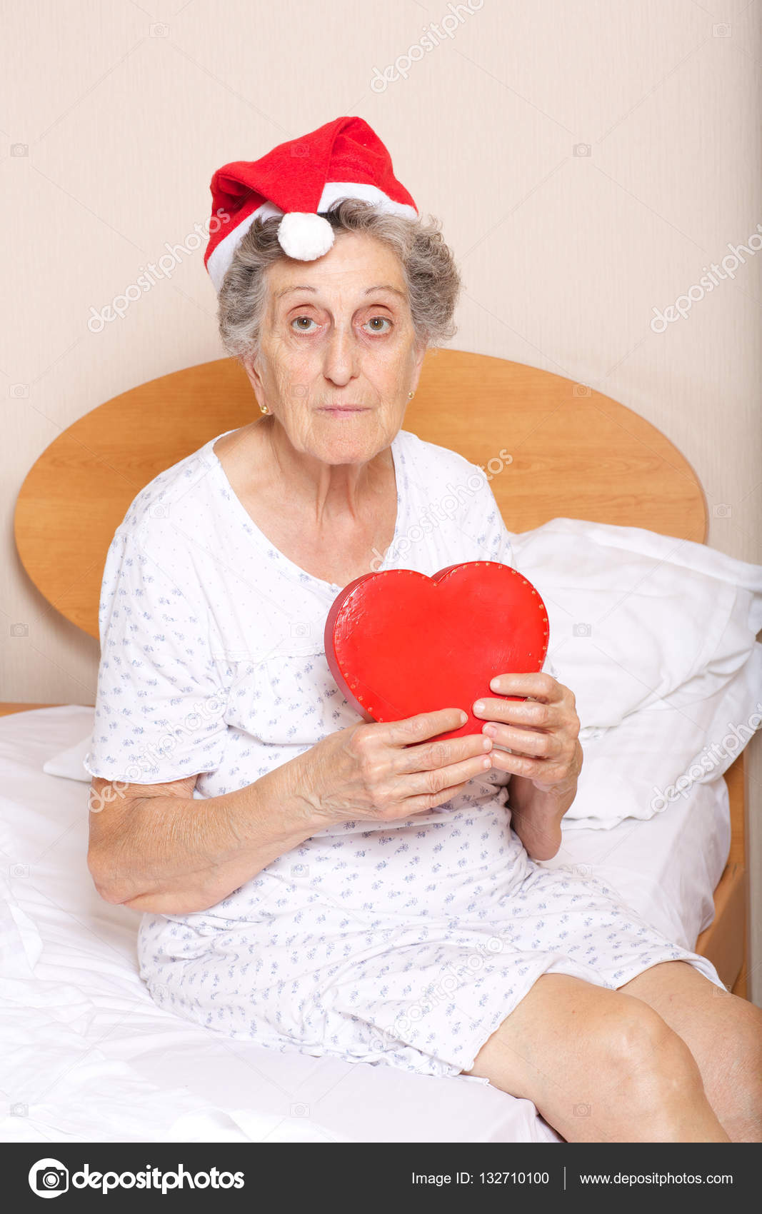 Old woman dressed in santa hat with red heart in her hands — Stock Photo 75ba174a8bf