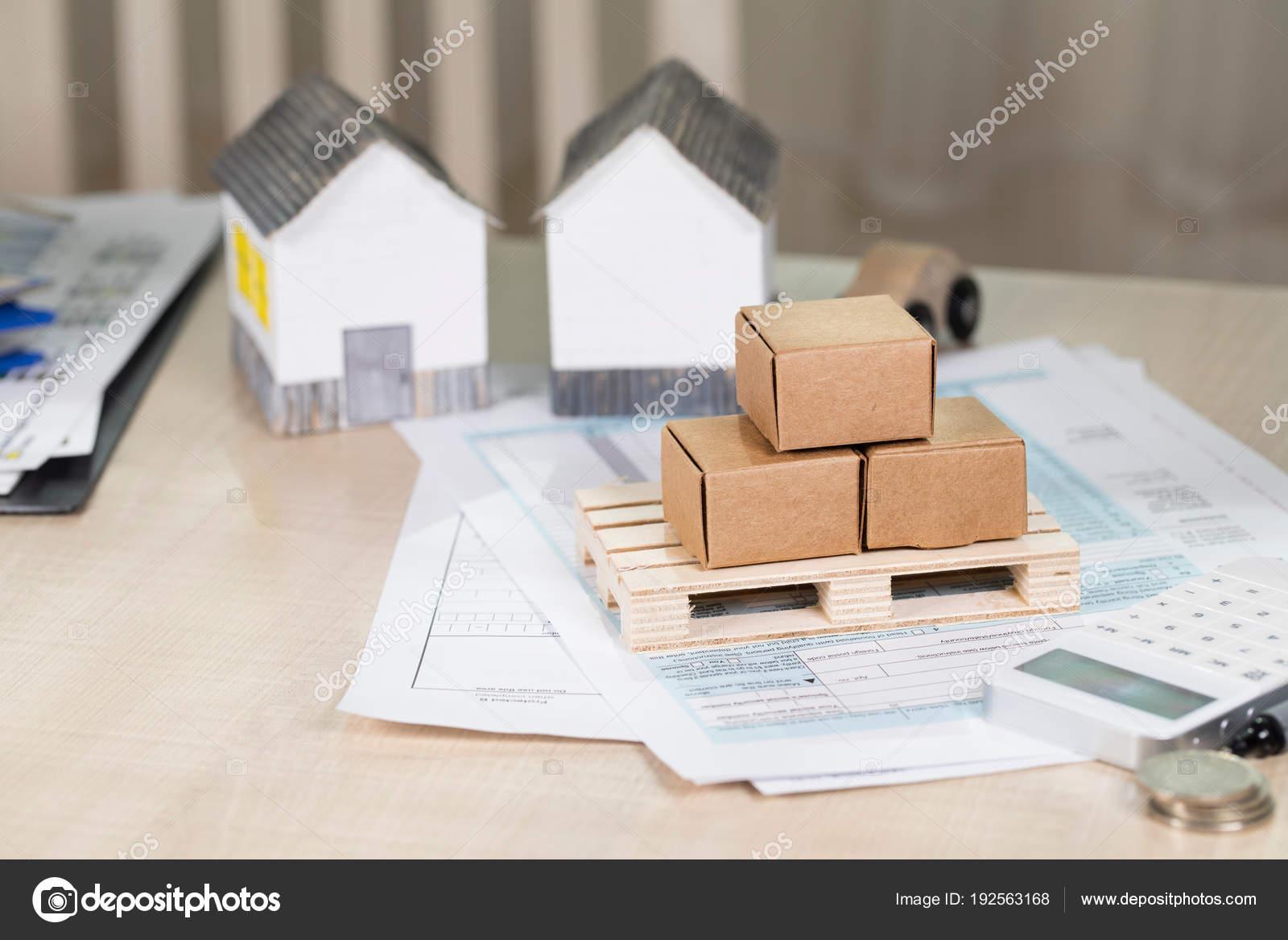 Pallet con scatole di cartone davanti alle case di carta piccolo