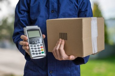 Package delivery concept. Man holds cardboard box and payment terminal in hands.