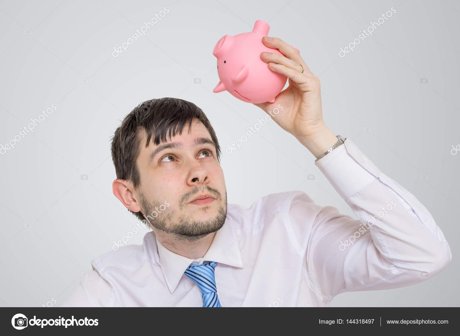 Jeune homme cherche en banque vide argent piggy– images de stock libres de  droits 66939e3190d