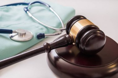 Gavel and stethoscope in background. Medical laws and legal conc