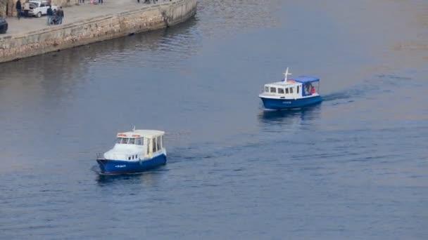 Jeden po druhém se plavat dva motorové čluny. Klidný provoz člunů na city bay. Lidé a auta se pohybují na molu