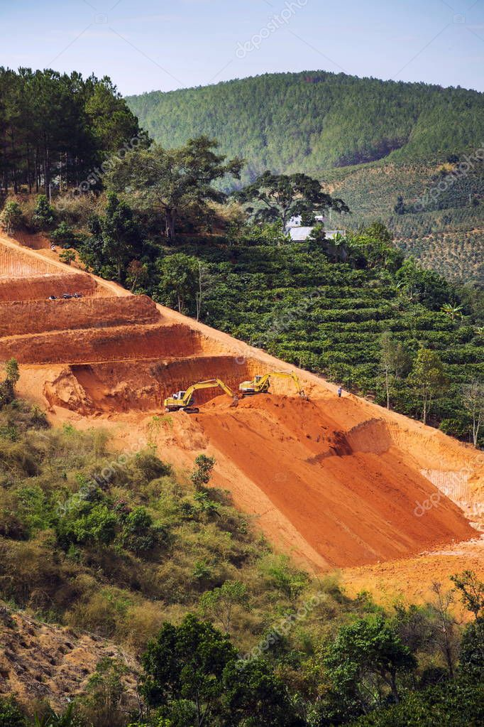 Excavators dig terraces for coffee beans plantations in Vietnam