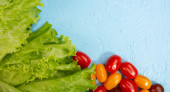šťavnaté listy salátu a zralé cherry rajčata na světle modrém texturovaném pozadí