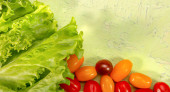 juicy lettuce leaves and ripe cherry tomatoes on a light green textured background