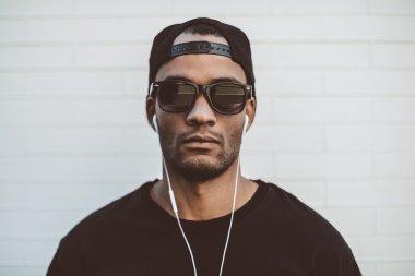 handsome African man in cap and headphones