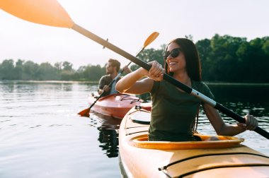 beautiful couple kayaking on river together