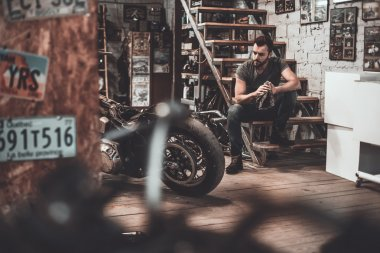 biker sitting on stairs in workshop
