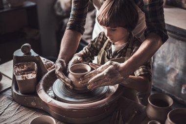 father and son making ceramic pot