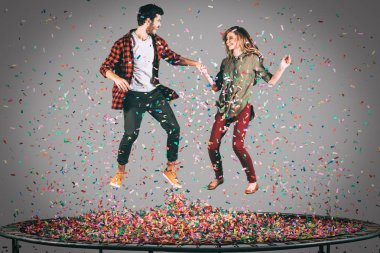 cheerful couple jumping on trampoline