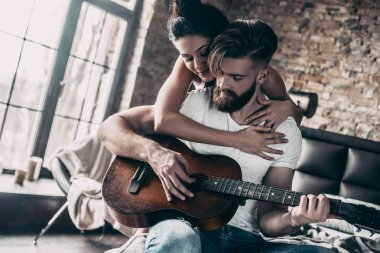 couple with acoustic guitar in bed