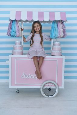 little girl sitting on candy cart