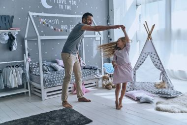 father and daughter dancing in bedroom