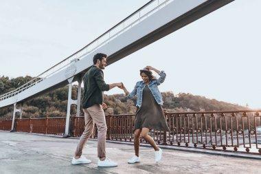 casual couple dancing on bridge