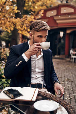 handsome business man drinking coffee while sitting in restaurant outdoors