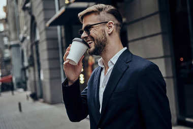 smiling Handsome business man drinking coffee while standing outdoors