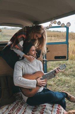 man with guitar in retro style mini van car, blonde girlfriend embracing him