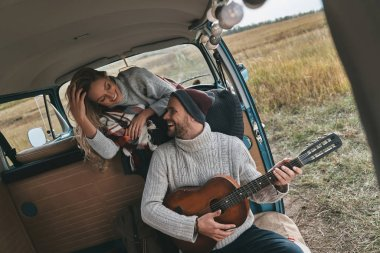 man playing new song on acoustic guitar for his girlfriend in retro style mini van car