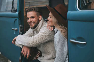 Beautiful young woman looking at her boyfriend and smiling while sitting in blue retro style mini van
