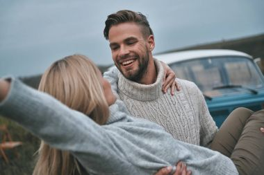 man carrying his attractive girlfriend and smiling near mini van car