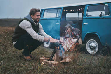 man warming up by the bonfire while woman reading a book in car transporter