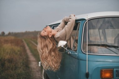 beautiful blonde woman leaning out the mini van window while enjoying the car travel