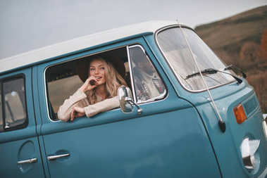 beautiful young couple in love enjoying travel in vintage car