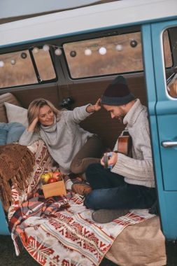 man playing new song on acoustic guitar for his girlfriend in blue retro style mini van car