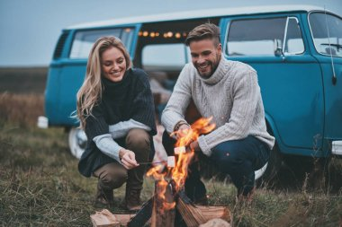Beautiful young couple roasting marshmallows over a campfire