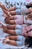 Draufsicht von vier Frauen im Schlafanzug auf dem Bett liegend, Teilansicht menschlicher Beine und Po in kurzen Hosen