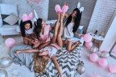 Fotografia giovani donne allegre cercando di mettere sulle orecchie del coniglietto sulla loro fidanzate del piede mentre era seduto sul letto