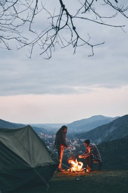 Beautiful young couple warming up by the campfire while camping in the mountains