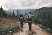 Pohled zezadu na páru s batohy chůzi po silnici v horách destinace
