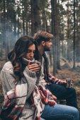 Schöne junge Paar Tassen mit heißen Getränken in Wald halten