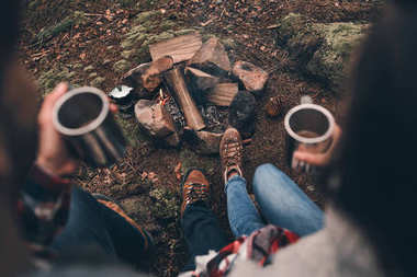 top view of people warming up near the campfire with hot drinks in cups