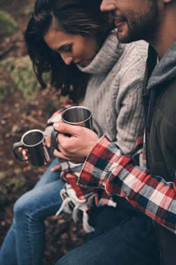 Beautiful young couple holding cups with hot drinks in forest