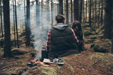 back view of  loving couple sitting in forest near campfire