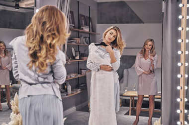 Attractive blonde woman choosing wedding dress in fitting room with bridesmaid