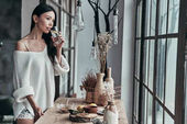 Attraktive junge Frau Trinkwasser mit Zitrone und stand in der Nähe der Fenster zu Hause