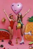 Fotografie Hravé holky v plavky drží balónky a při pohledu na fotoaparát s úsměvem stoje růžové pozadí