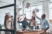 Dokázali jsme to! Skupina mladých jistý podnikání lidí, házení papíru ve vzduchu při práci za skleněnou stěnou v zasedací místnosti