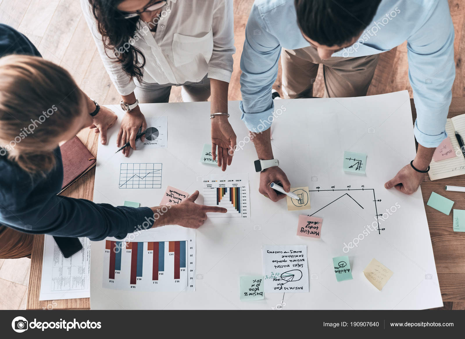 Going details close top view young confident business people working going over details close up top view of young confident business people working together while man writing on blueprint in the office photo by malvernweather Images