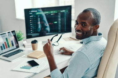 Handsome young African man in shirt looking at camera and smiling while working in the office