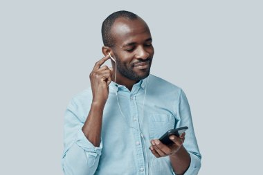 Charming young African man listening music using smartphone and smiling while standing against grey background