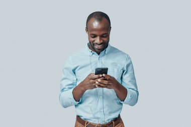 Happy young African man listening music using smartphone and smiling while standing against grey background