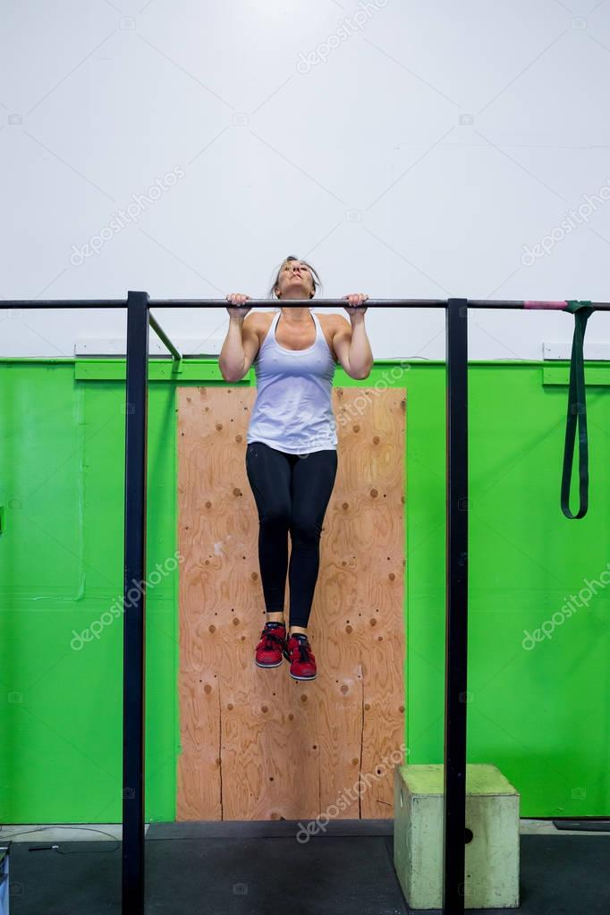 Fit woman doing exercises and pullups on a pullup bar at a crossfit gym for females.